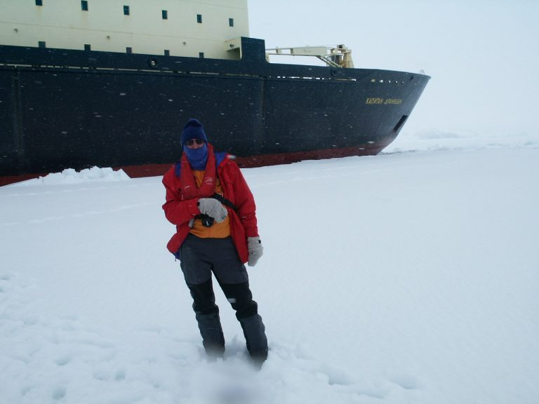 Man on frozen sea ice with icebreaker in backbround