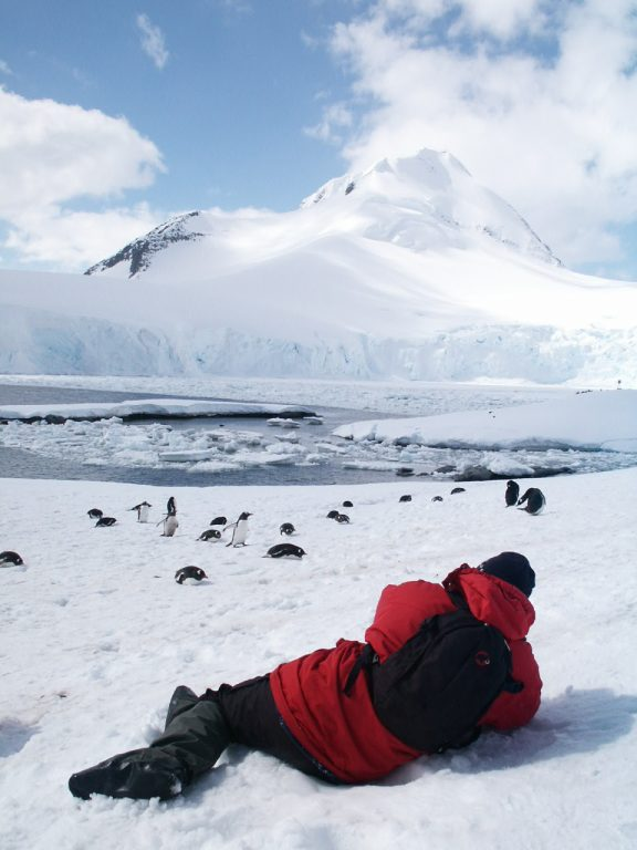 photographer lying down on ice to photograph penguins