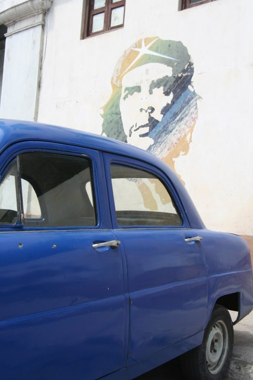blie car and Che mural on wall