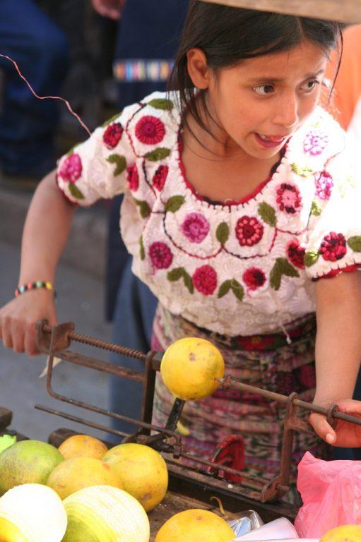 young girl making orange juice