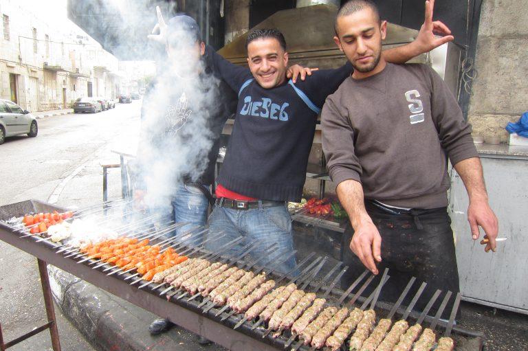 two men cooking kabobs