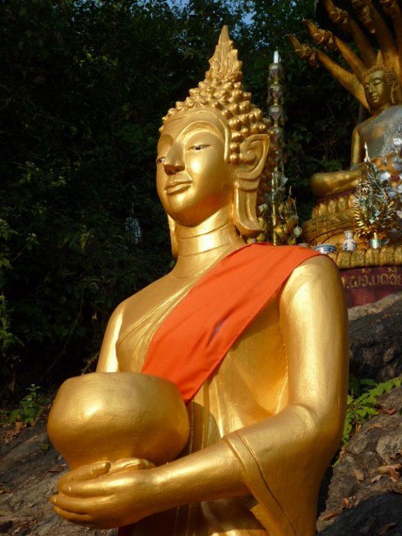 Laos, statue w alms bowl