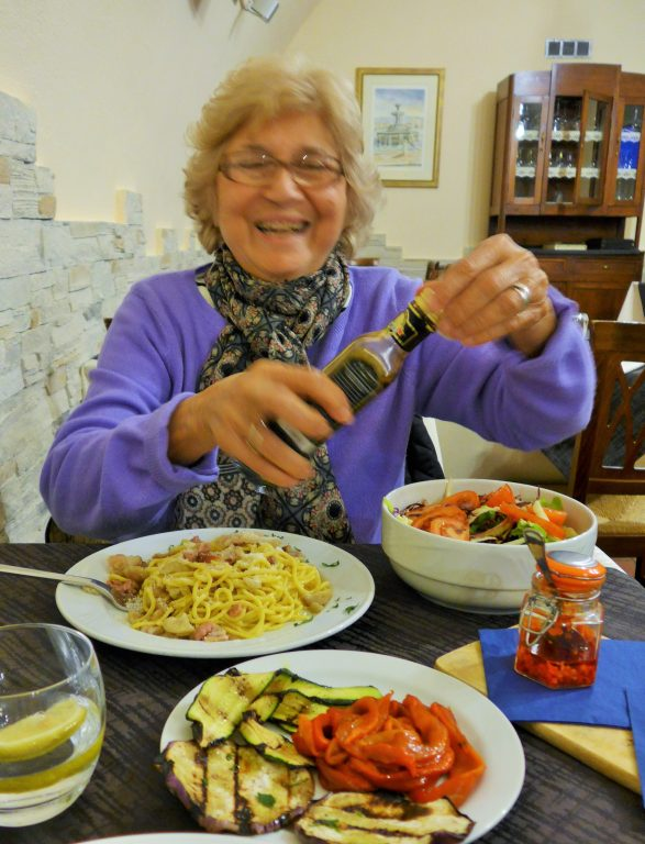 older woman with dinner spread